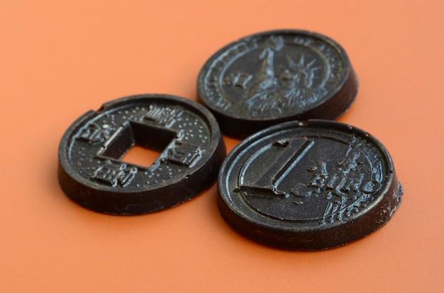 ユーロ、アメリカ、日本のコインの形をした3つのチョコレート製品がオレンジ色のプラスチック製の背景にあります