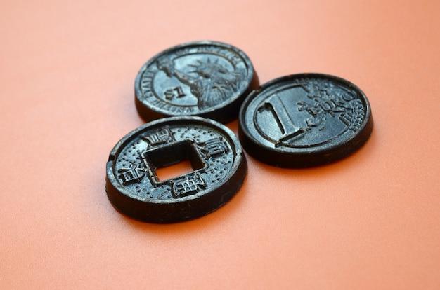 ユーロ、アメリカ、日本のコインの形をした3つのチョコレート製品がオレンジ色のプラスチックの背景にあります。食用の形の現金硬貨のモデル