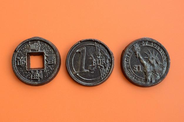 ユーロ、アメリカ、日本のコインの形をした3つのチョコレート製品がオレンジ色のプラスチックの背景にあります。