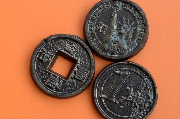 ユーロ、アメリカ、日本のコインの形の3つのチョコレート製品がオレンジ色のプラスチックの上にあります