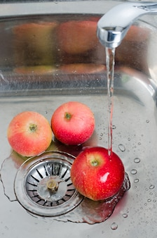 食品衛生水の流れの下で金属製のシンクの3つの赤いリンゴ。縦の写真