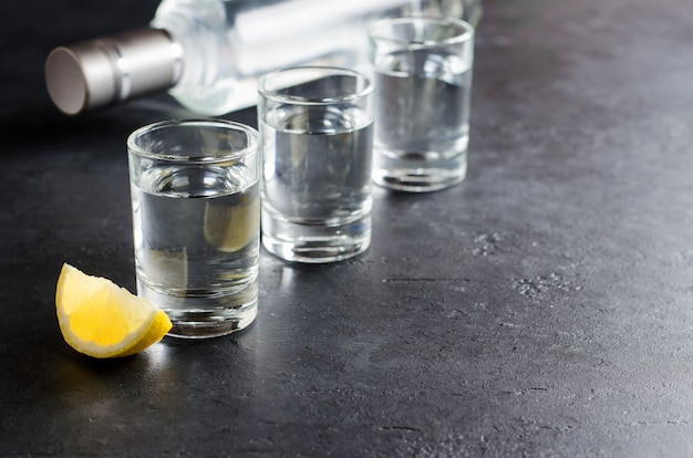3つのメガネ、ウォッカのボトル、暗い背景にレモンの部分。