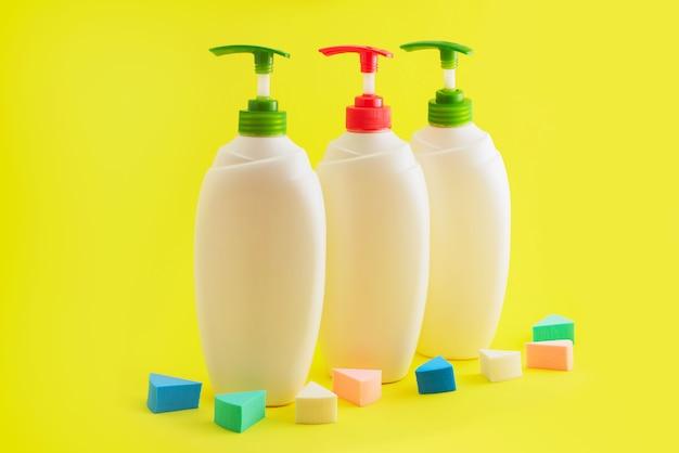 黄色の背景にディスペンサーと3つのプラスチック製のボトル。