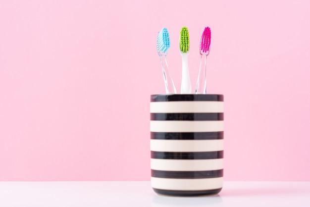 ピンクの背景にガラスの3つのプラスチック製のカラフルな歯ブラシをクローズアップ