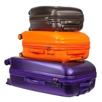 白で隔離される3つのポリカーボネートスーツケースから成る荷物