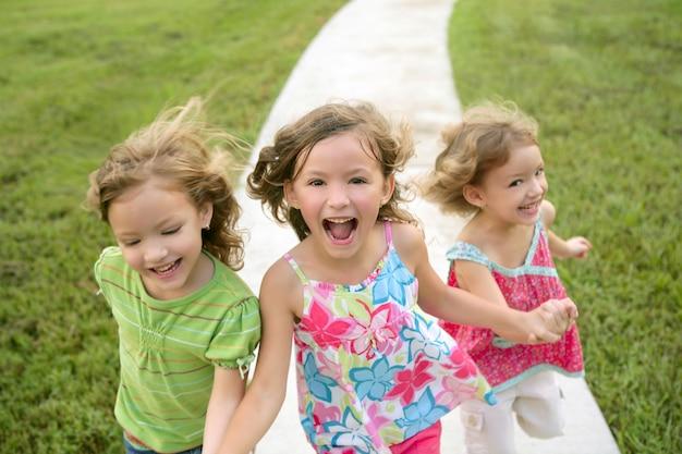 公園を走って遊んでいる3人の姉妹の女の子
