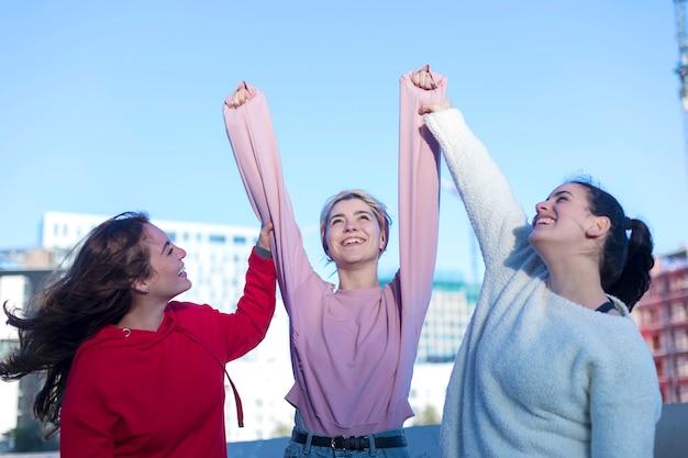 屋外のカジュアルな服装で3人の幸せな興奮した若い成人女性。