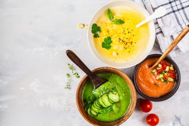 灰色のコーン、キュウリ、ガスパチョのスープのボウルに3種類の野菜クリームスープ、