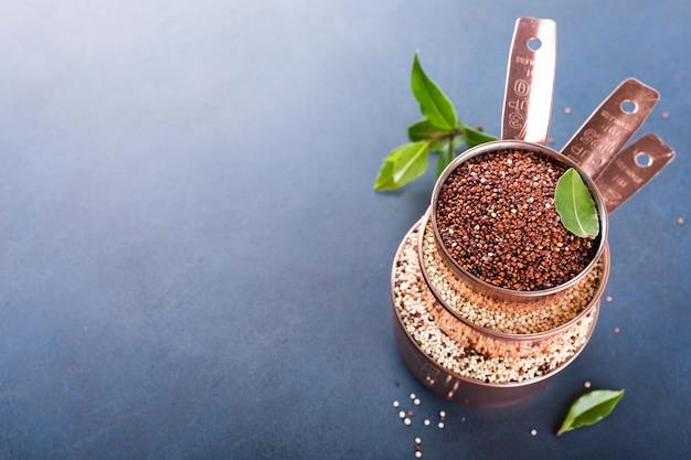 生キノアが混合された3つの銅計量カップのスタック