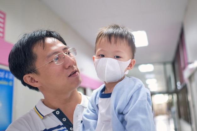 Отец держит милый маленький азиат 3-х лет малыш мальчик носить защитную медицинскую маску, родитель и больной ребенок