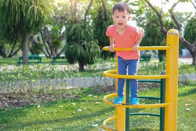 屋外の遊び場で登山フレームに登って楽しんでかわいいアジア3歳幼児赤ちゃん男の子