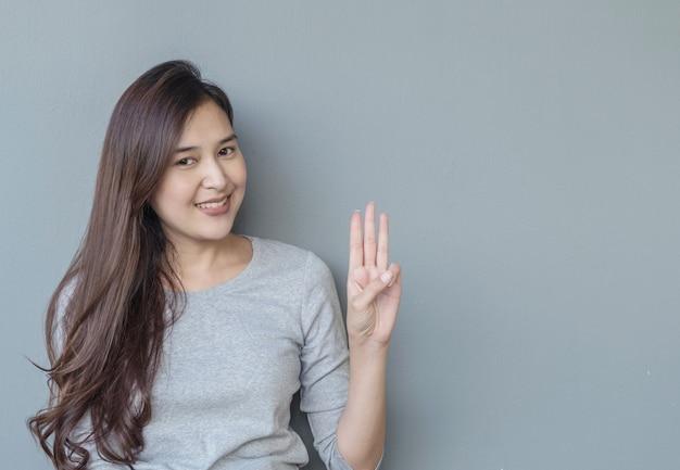 クローズアップ女性はセメント壁テクスチャ背景に笑顔で3本の指を保持します