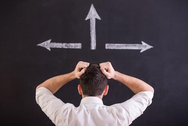 自信を持って男は3つの矢印の下に立っています。