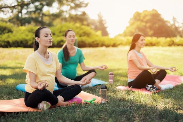 3人の妊娠中の女性は蓮のポーズでヨガマットの上に座る