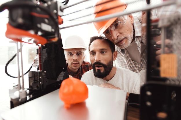 3人の男性が印刷モデルの作成に取り組んでいます