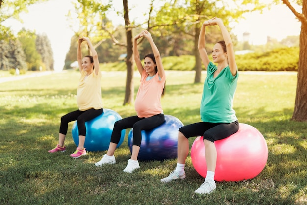 3人の妊娠中の女性は、ヨガのボールで公園に座っています。