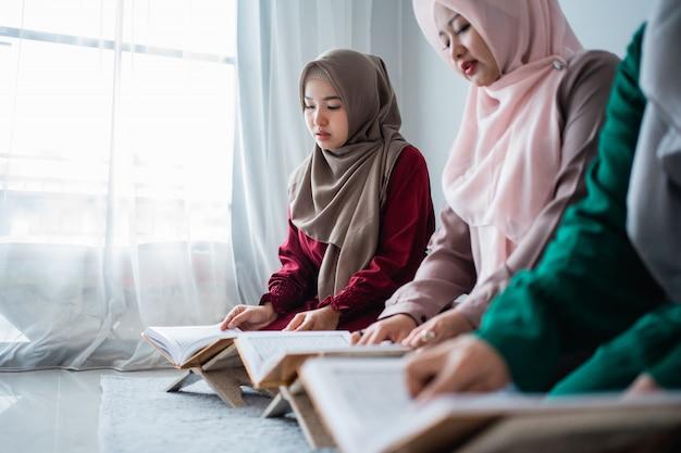 3人のアジアのイスラム教の女性が一緒にアルコーランの神聖な本を読んで学ぶ