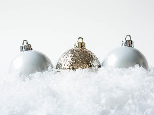 雪の中で3つのラウンドクリスマスボール。メリークリスマスまたは新年あけましておめでとうございます組成。コピースペース