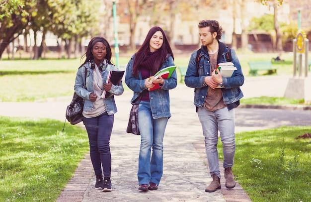 屋外の公園で3人の学生