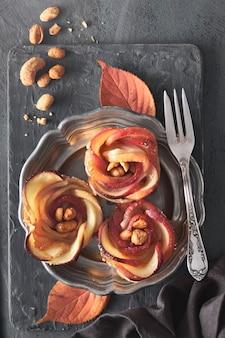 金属板にバラの形をしたリンゴのスライスと3つの自家製のパイ生地、フラットレイアウト
