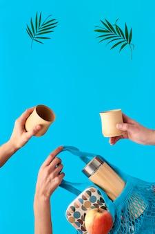 シュロの葉で活気に満ちた青いミントの壁にシュールな浮上。竹のコップが付いている3つの手。環境に優しい断熱された竹製のフラスコに廃棄物ゼロのお茶。ランチボックスとティーフラスコが入ったネットバッグ。