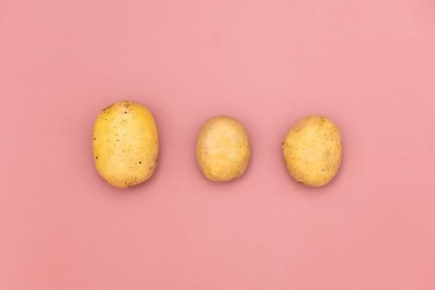 ピンクの背景の3つのジャガイモ