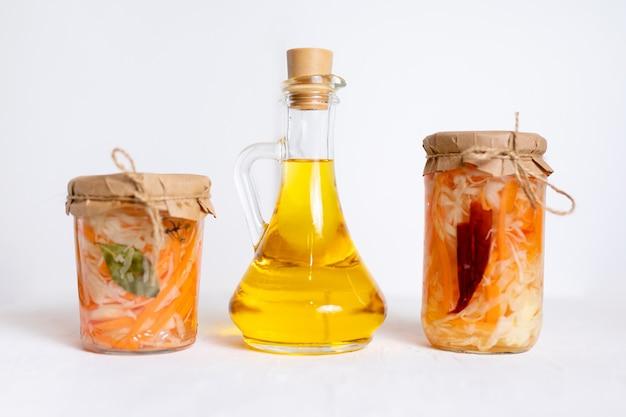 ザウアークラウトとニンジンの3つのジャールと、ジュースとオイルのボトル、白い木製テーブル。伝統的な自家製