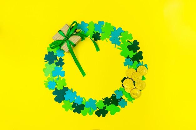 聖パトリックの日。緑の3つの花びらのクローバー、ギフトボックス、背景に横たわっている金貨の円形