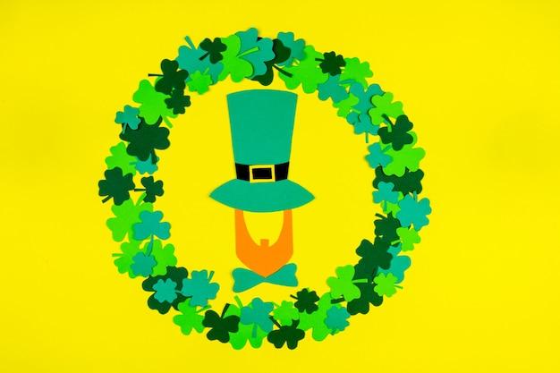 聖パトリックの日。緑の3つの花びらのクローバーの円の形で横になっている帽子のレプラコーンのシルエット