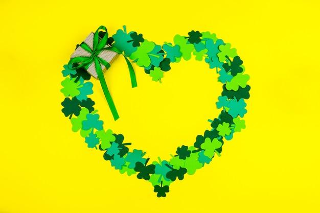 聖パトリックの日。黄色の背景に横たわっているギフトボックスと緑の3つの花びらのクローバーのハート