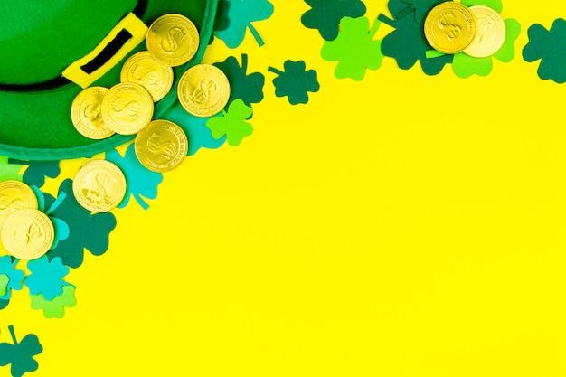 聖パトリックの日。金貨、緑の3つの花びらのクローバー、黄色の背景にレプラコーンの緑の帽子