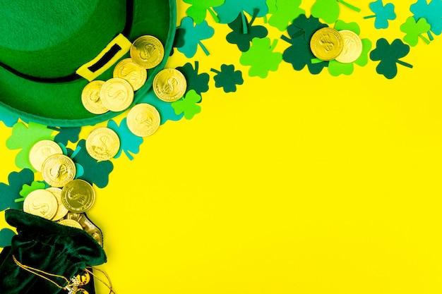 聖パトリックの日。ゴールドコイン、緑の3つの花弁のクローバー、黄色の背景にレプラコーンの緑の帽子と小さなバッグ
