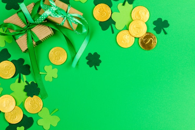 聖パトリックの日。緑の3つの花びらのクローバーと緑の背景の金レプラコーンコイン