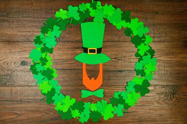 聖パトリックの日。緑の3つの花びらのクローバーの円形の木製テーブルの上に横たわる帽子のレプラコーンのシルエット