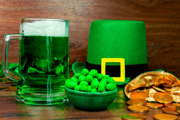 聖パトリックの日。ビールの緑のガラスパイント、緑のスナッククッキーお菓子、レプラコーンの緑の帽子、緑の3つの花びらのクローバー、木製のテーブルの上の金貨