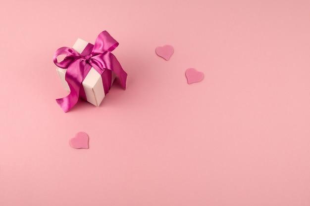 お祝いサテンリボン弓とコピースペースで柔らかいピンクの背景に3つのハートのトップビューギフトボックス