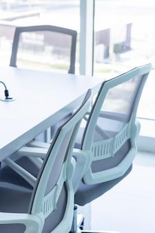 オフィスの3つのオフィスチェアと会議用テーブル。ビジネスや事務作業の概念。