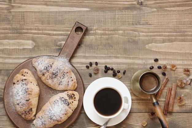3つのおいしい焼きたてのクロワッサンと木の板にコーヒーカップ。上面図。朝ごはん。コピースペース。