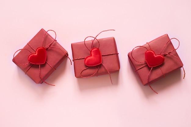 バレンタインの日の構成:3つの赤いギフトボックス、赤いロープの弓、パステルピンクの赤いハート。上面図。