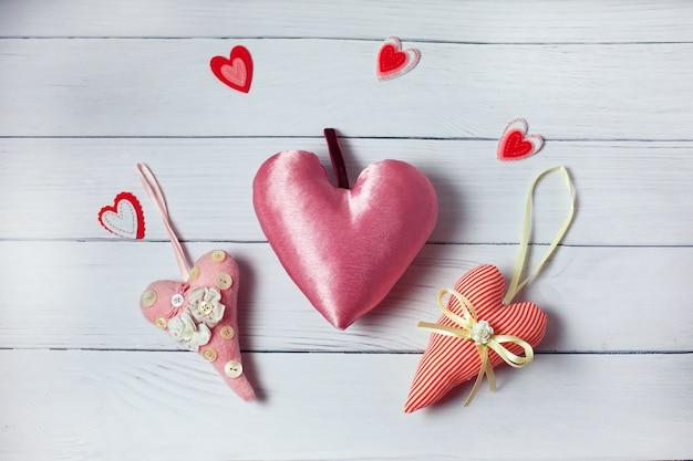 木製の背景に3つの繊維ピンクの心。ビンテージスタイルのバレンタインの日の装飾