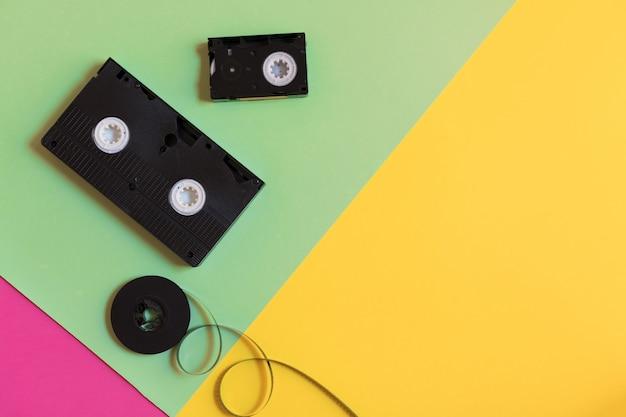 レトロなビデオカセットと3色パステル紙の背景上のフィルム。