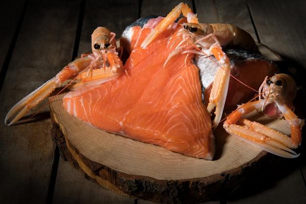 生のサーモンフィレの暗い背景、オメガ3の野生の大西洋の魚のソース、健康食品、ケトダイエットの概念