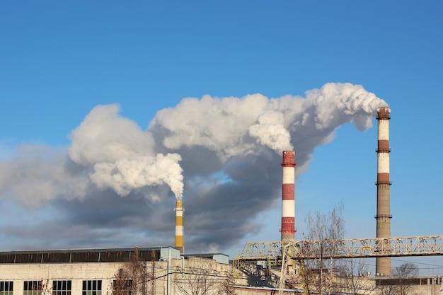 3つの工場の煙突から濃い煙が噴出した。