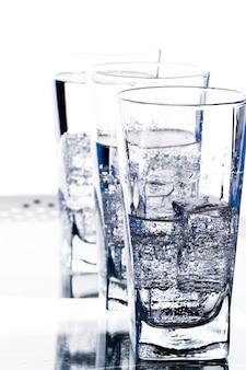 白い背景の上の冷たい水のクローズアップと3つのメガネ