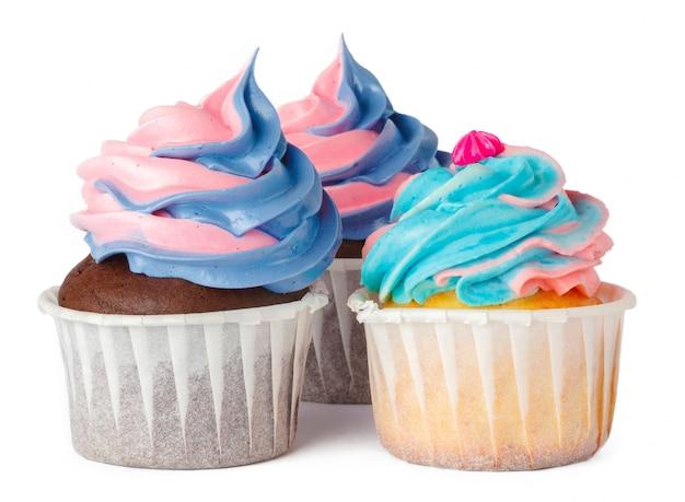 白で隔離クリームトッピングと3つのおいしいカップケーキ