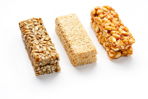 ピーナッツ、ゴマ、種子が並んだ穀物グラノーラバー。トップビュー3つの各種バー、分離