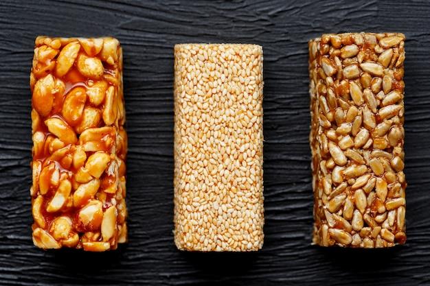 暗い石のテーブルのまな板の上のピーナッツ、ゴマ、ヒマワリの種を持つ穀物グラノーラバー。上からの眺め。 3つの盛り合わせバー