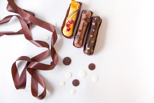 さまざまな詰め物やデザインの3つのエクレアのセットは、チョコレートの滴と茶色の絹のリボンで飾られた白い表面に分離します。