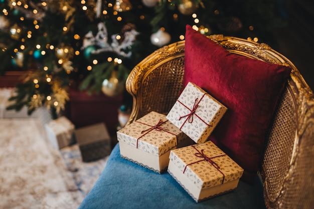 クリスマスのモミの木の近くの肘掛け椅子に3つのラップされたプレゼントボックス