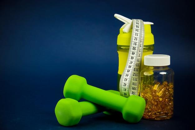 プラスチックシェーカー、緑のダンベル、オメガ3缶